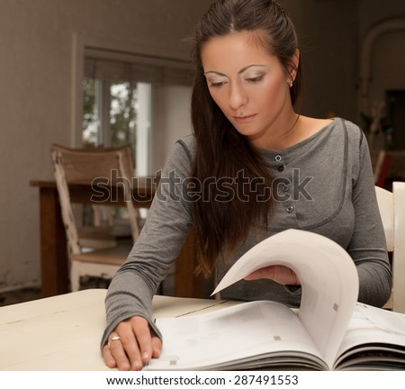 home  concept - smiling young  woman reading magazine at home - stock photo