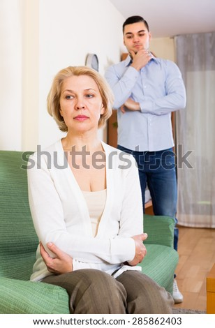 Home conflict between sad aged woman and her young boyfriend