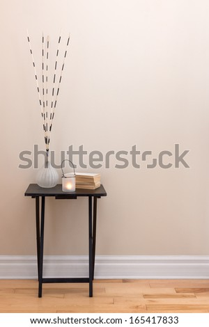 Home decor. Little table decorated with candlelight, vase and books. - stock photo