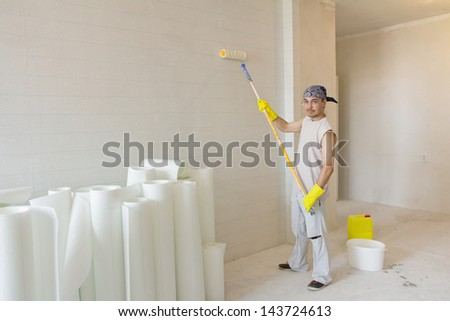 Home decoration. Worker painting wallpaper with painting roller - stock photo