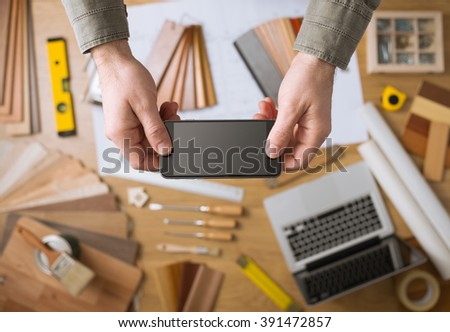 Home decorator's hands holding a mobile touch screen phone, desktop with tools, laptop and wood swatches on background, top view - stock photo