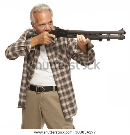 HOME DEFENSE   Shotgun in the hands of a mature male adult, ready to fire. Gun owner protecting his home or loved ones with a firearm. - stock photo
