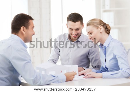 home, design and architecture concept - couple looking at blueprint and model of their new house at office - stock photo