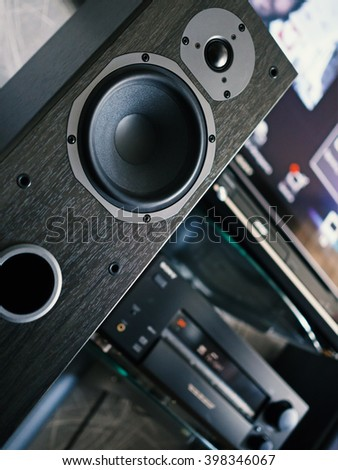 Home entertainment center. Close-up audio speaker. Shallow depth of field. Low angle verical tilt view. - stock photo
