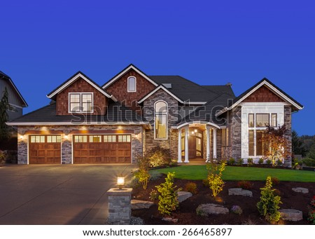 Home Exterior at Night: New Luxury House at Night with Deep Blue Sky, Three Car Garage, Columns, Gables, Green Lawn, Landscaping, and Driveway - stock photo