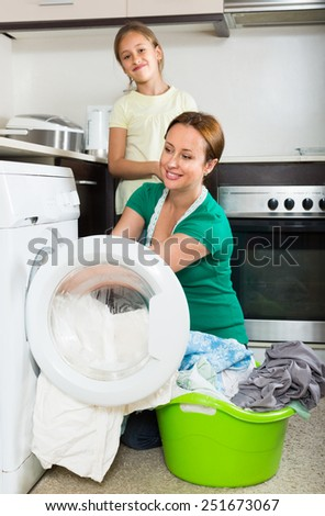 Home family laundry. Happy mother with daughter loading clothes into washing machine in kitchen - stock photo