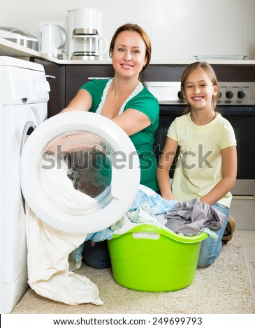 Home family laundry. Happy mother with smiling preschooler daughter loading clothes into washing machine in kitchen - stock photo