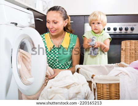 Home family laundry. Smiling mother with daughter loading clothes into washing machine in home. Focus on woman  - stock photo