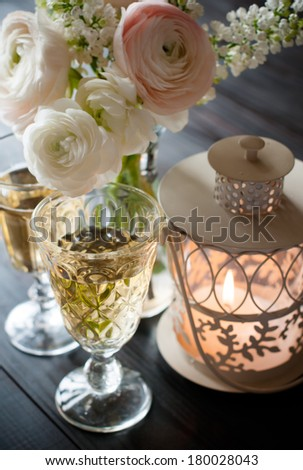 Home festive wedding decor, exquisite bouquet of flowers, buttercups and white lilacs, two wineglasses and lantern candle on a dark wooden board - stock photo
