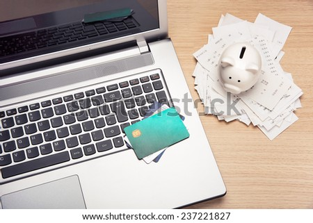 Home finance scene with piggy bank, bills alnd laptop - stock photo