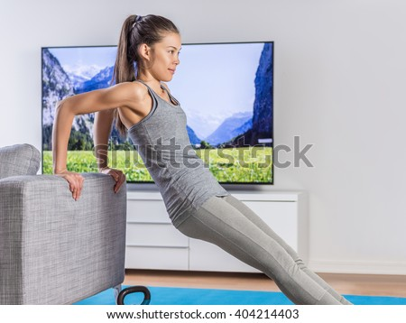 Home fitness woman strength training arms watching online tv dvd workouts doing bodyweight exercises in living room using sofa to do triceps exercise. Exercising Asian girl in her apartment indoors. - stock photo