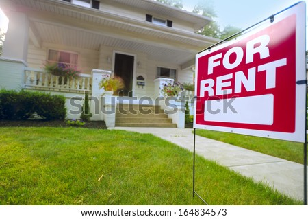 Home For Rent Sign in Front of Beautiful American House - stock photo