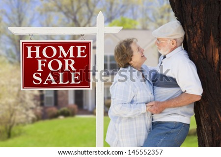 Home For Sale Real Estate Sign with Happy Affectionate Senior Couple Hugging in Front of House. - stock photo