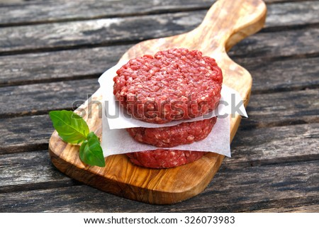 Home HandMade Minced Beef burgers on cutting board. old wooden table - stock photo