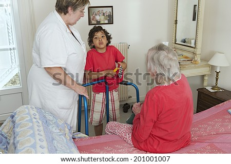 home hospitalization-grand son visiting his grand mother with care giver  - stock photo