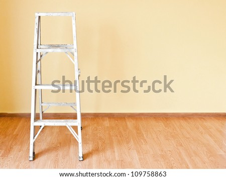 Home improvement concept with ladder and yellow wall - stock photo