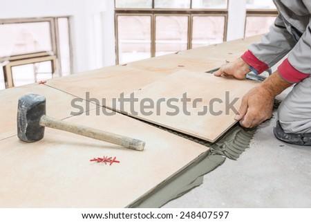 Home improvement, renovation - handyman laying tile, trowel with mortar - stock photo