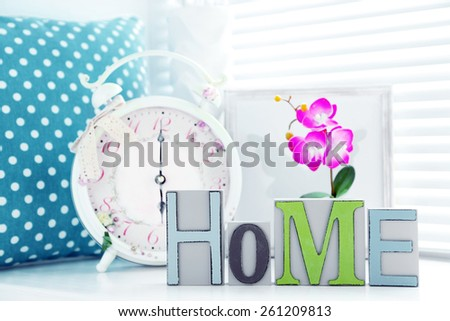 Home in colorful letters in light white interior - stock photo