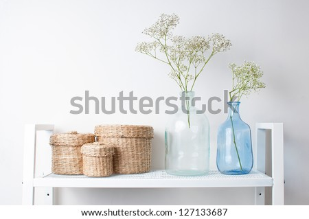 home interior decoration: the branches in vintage bottles and baskets on white shelves - stock photo