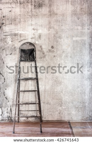 Home interior room repair concept - old gray concrete wall and dirty floor in repairing room with old dirty black stepladder near the wall closeup view  - stock photo