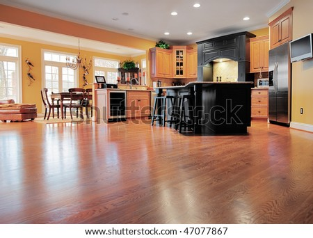 Home interior shows a large expanse of wood flooring in the foreground and a kitchen and dining room in the background. Horizontal format. - stock photo