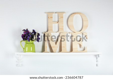 Home interior: stylish shelf with bouquet of wildflowers and wooden letters  - stock photo