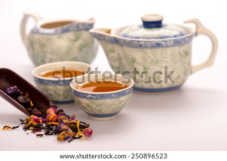 Home is where the tea is. Beautiful composition of Chinese traditional crockery teapot and cups surrounded by flowering tea isolated on white background with selective focus - stock photo