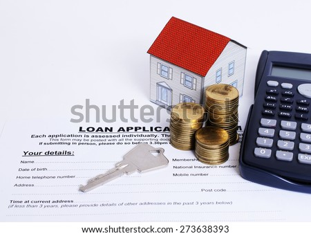 Home key and coins stack and paper house and calculator on Loan application form for loan concept - stock photo