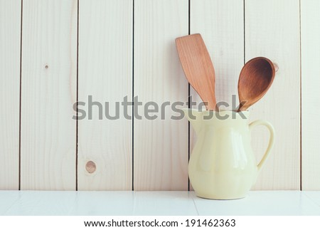 Home Kitchen Decor: vintage cutlery, kitchen utensils in yellow ceramic jug on a wooden board background , cozy arrangement retro style, soft pastel colors. - stock photo