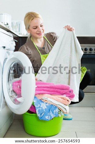 Home laundry. Happy blonde woman loading clothes into a washing machine in home  - stock photo