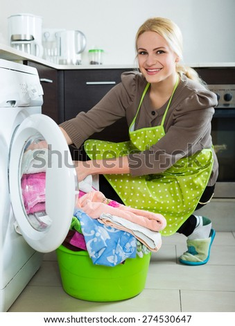 Home laundry. Smiling american  girl using washing machine at home - stock photo
