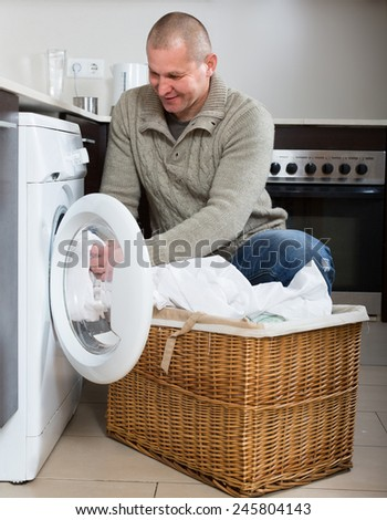 Home laundry. Smiling guy using washing machine at home - stock photo
