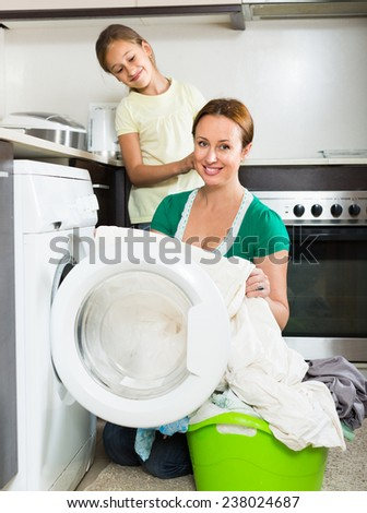Home laundry. Smiling woman with daughter using washing machine at home - stock photo