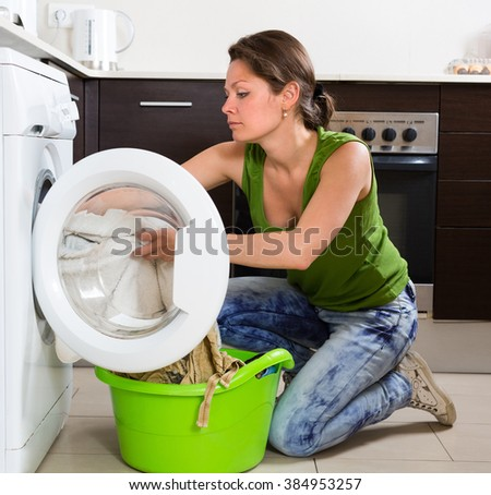 Home laundry. Young housewife using washing machine at home