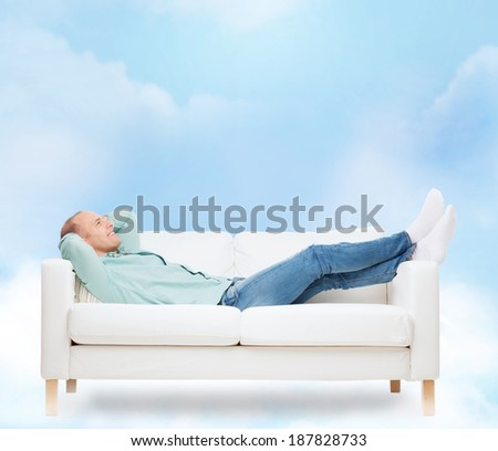home, leisure and happiness concept - smiling man lying on sofa - stock photo