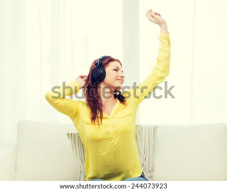 home, leisure and happiness concept - smiling teenage girl sitting on sofa with headphones - stock photo