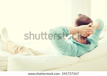 home, leisure, relax and happiness concept - man lying or sitting on sofa at home from back - stock photo