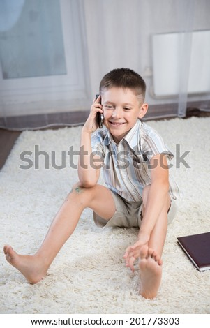 home, leisure, technology and internet concept -Smiling boy indoor. Sitting on the floor with book and talking on the phone - stock photo