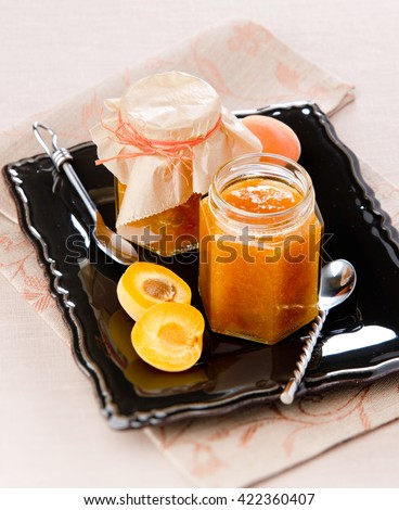 home-made apricot jam in a glass jar on a black plate with apricot halves close - stock photo