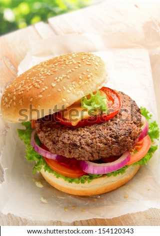 Home made burger made with pure ground beef. Garnished with red onion, tomato and lettuce on a hamburger bun, topped with sesame seeds.  - stock photo