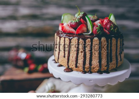 Home made cake/cheesecake decorated with strawberries, lime and chocolate - stock photo