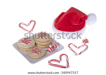 home made candy cane stripped peppermint flavor sugar cookies on a square plate with santa hat and small candy canes shaped like hearts isolated on a white background - stock photo