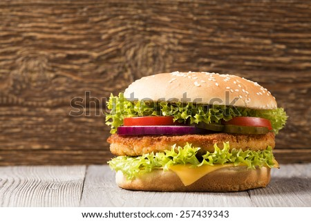 Home made chicken burger with cheese, lettuce, tomato and onion on wooden board - stock photo