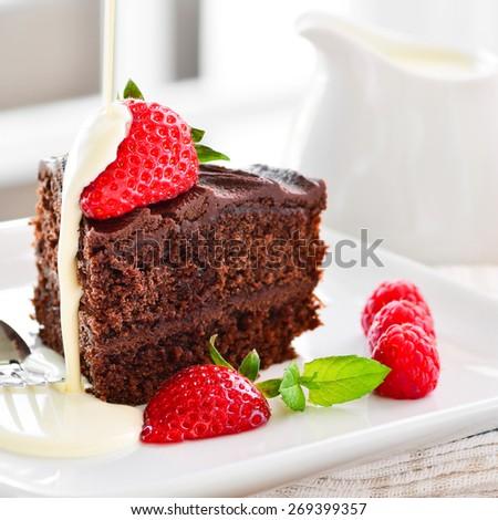 Home made chocolate cake with fresh cream strawberries and raspberries - stock photo