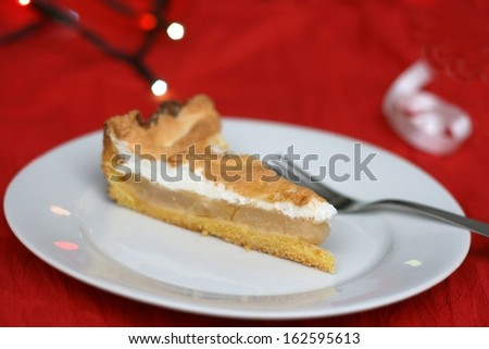 Home made christmas apple pie with whipped egg white, christmas lights and decoration in the background, shallow DOF - stock photo