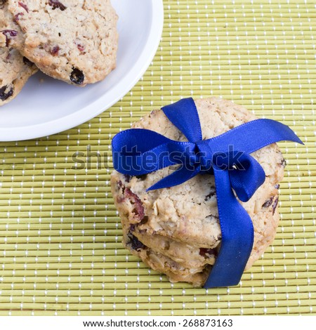 Home made cranberry biscuits with blue ribbon and on a plate. - stock photo