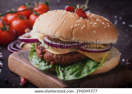 Home made freshly cooked burger with seasoning, vegetables and greens on wooden board, black background  - stock photo
