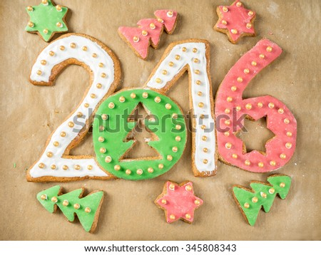 Home-made gingerbread cookies in shape of 2016 New Year digits on baking paper - stock photo