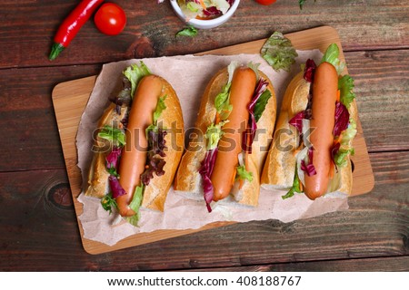 home made Hot dog - sandwich with lettuce on wooden background - stock photo