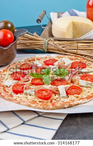 Home made raw pizza with prosciutto and blue cheese. The dough with the addition of fiber and Provencal herbs - stock photo